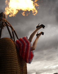 Legs sticking out of a hot air balloon basket with flame and storm clouds
