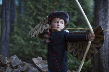 Boy playing with bow and arrow in forest
