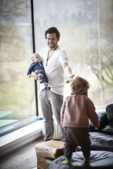 Smiling father with two children at home