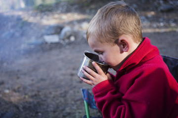 A little boy wearing a red sweater drinking out of a tin cup at the campfire at his campsite while camping in the mountains