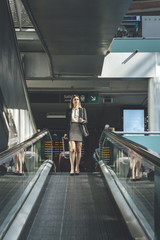 Young business woman walking through mechanical stairs at train station with mobile phone in her hand, a handbag and suitcase