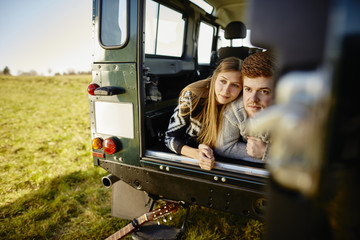 Young couple lying in car parked on meadow