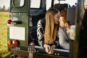 Young couple kissing in off road vehicle