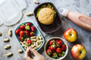 Cooking lunch for the child to school. On the gray kitchen table. Sandwich, strawberries and peanuts in lunchboxes. Top view. Woman puts strawberries in a container