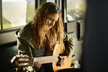 Young woman playing guitar in off road vehicle