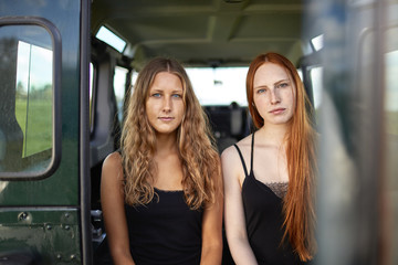 Two young women sitting in trunk of off road vehicle
