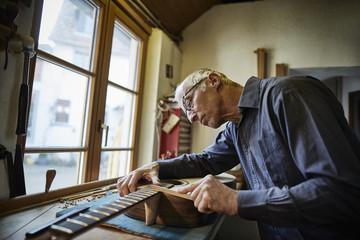 Guitar maker in his workshop at work