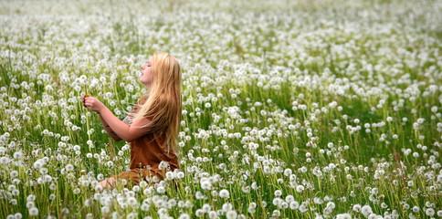 dandeliondream, longhaired pretty girl sitting in a field of dandelion