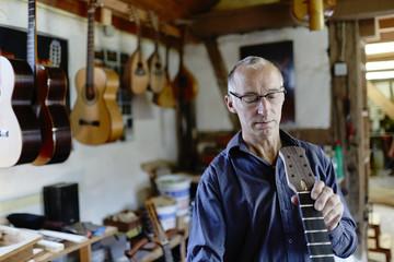 Guitar maker examining guitar in his workshop