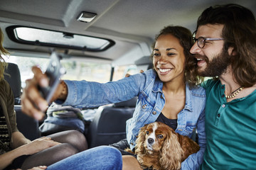 Happy couple with dog taking a selfie in car