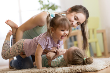 Family - mom and daughters having a fun on floor at home. Woman and children relaxing together.