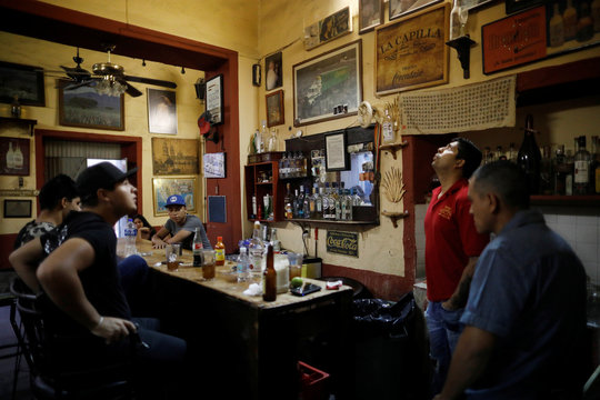 Customers stand next to bottles of different brands of tequila in La Capilla bar in Tequila