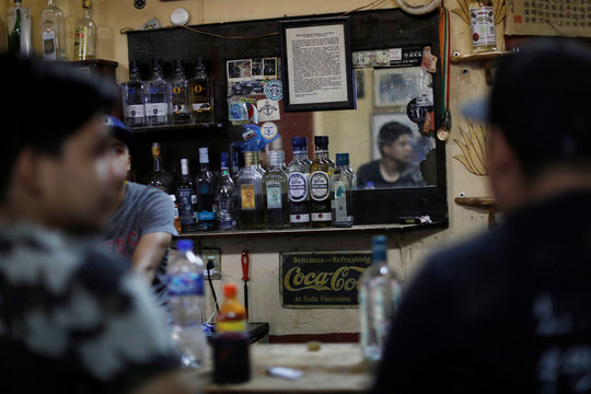 Bottles of different brands of tequila are seen next to customers in La Capilla bar in Tequila