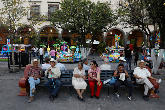 People are seen sitting on a bench in Tequila