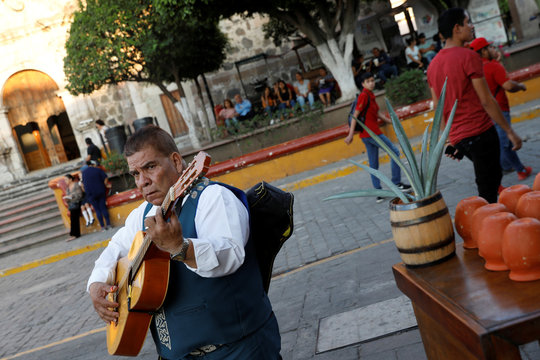 A mariachi musician plays his guitar on a street in Tequila