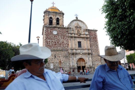 Men are seen sitting on a bench in front of the cathedral in Tequila