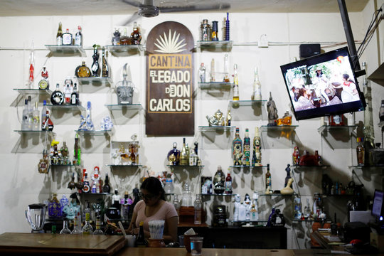 A bartender stands next to bottles of tequila in Don Carlos bar in Tequila