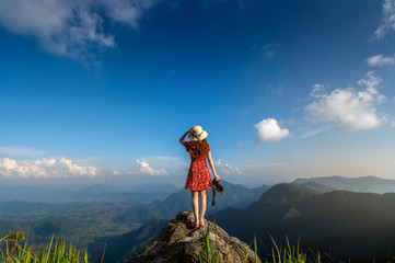 Wall Mural - Woman hand holding camera and standing on top of the rock in nature. Travel concept.