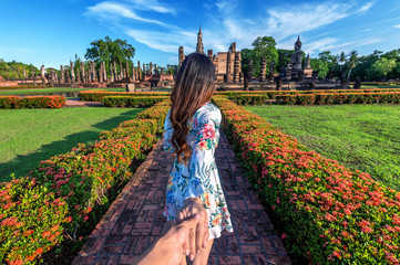 Wall Mural - Woman holding man's hand and leading him to Wat Mahathat Temple in the precinct of Sukhothai Historical Park, Wat Mahathat Temple is UNESCO World Heritage Site, Thailand.