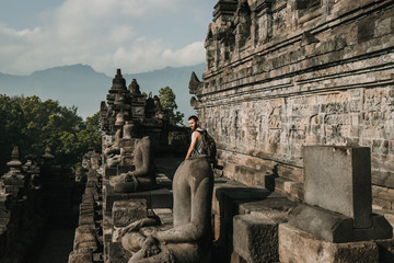Handsome young tourist feeling the peace of the great Borobudur temple, historical famous place in the java island Indonesia. Lifestyle and travel photography.