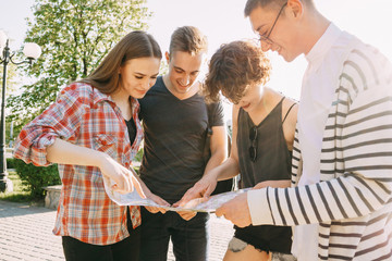 Traveling, sightseeing, group travel, city tour, student exchange program, togetherness. Group of friends searching the location on city map.