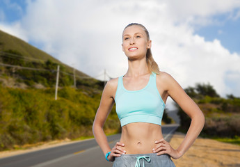 fitness, sport, friendship and healthy lifestyle concept - happy young woman doing sports over big sur hills and road background in california