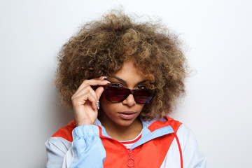 Close up black female fashion model posing with sunglasses against white wall