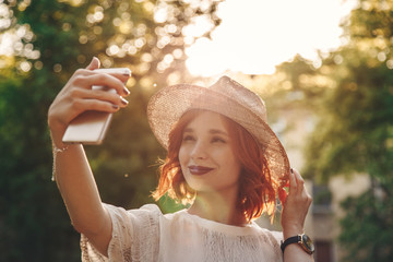 Beautiful and stylish girl taking a selfie with her phone outdoors