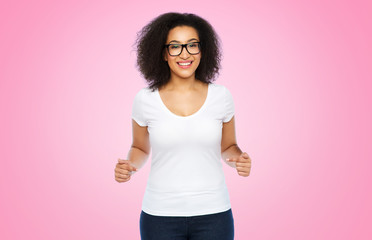 body positive and people concept - happy african american woman in white t-shirt and glasses pointing fingers to herself over pink background