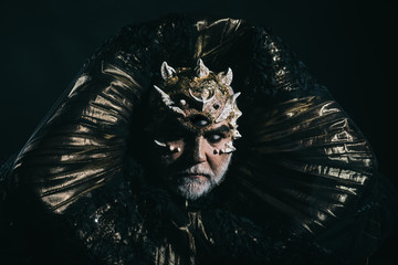 Alien, demon, sorcerer makeup. Man with third eye, thorns or warts. Demon with golden collar on black background. Horror and fantasy concept. Senior man with white beard dressed like monster.