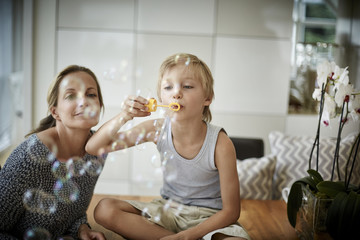 Boy with mother blowing soap bubbles