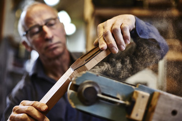 Guitar maker grinding fingerboard in his workshop