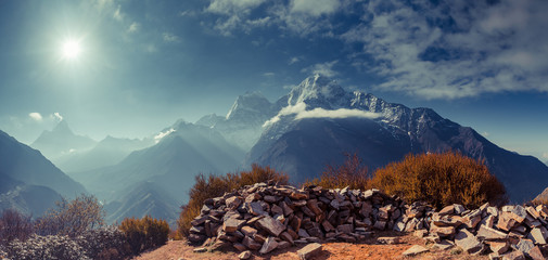 Wall Mural - The gorgeous scene the boulders on the mighty misty snow-covered mountain background. The Himalayas. Everest Base Camp trek in the Sagarmatha National Park in the north-eastern Nepal.
