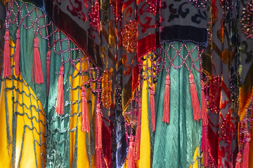 Brightly colored and saturated boho background with layers of fabrics and tassels and net