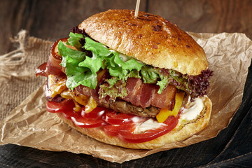 Closeup of a burger with meat and cheese and fresh green grass.