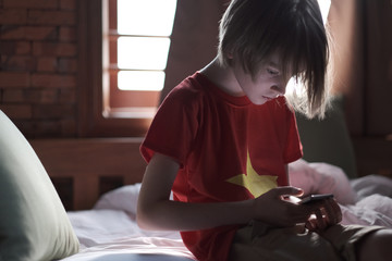 The face of the child, illuminated by the screen of the phone in his hands