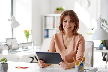 business, technology and people concept - businesswoman with tablet pc computer working at office
