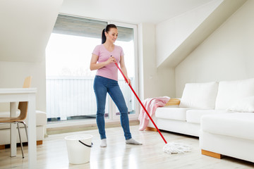people, housework and housekeeping concept - happy woman or housewife with mop cleaning floor and dancing at home
