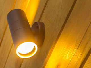 Outdoor exterior small cylinder lamp on wooden wall. External illumination Fotomurales
