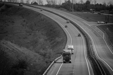 Trucks driving on the highway delivering goods. Black and white