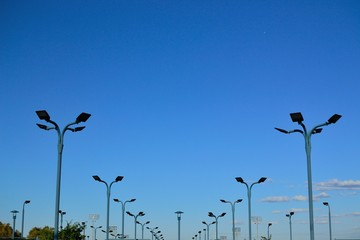 Symmetrical image of poles with lights at a tennis court. The lights are configured as pairs and quads and result in an interesting aesthetic, with a few puffy clouds on a blue sky