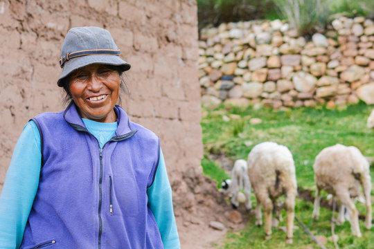 Happy native american farmer with her sheep in the countryside.