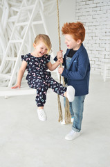 Cute kids red boy brother and blonde sister have a fun on the swing in the white studio