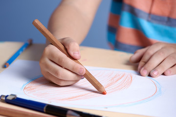 Close view of a boy drawing with pencils.