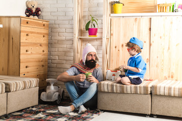Father and son playing doctor at home. Dad with tea mug listening to kid dressed as nurse. Physician with serious face giving instructions to bearded man in denim outfit, medical treatment concept