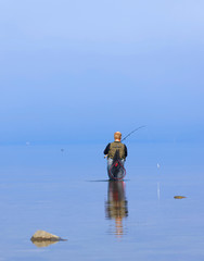 Angler wearing waders in the blue calm sea trying to catch trout