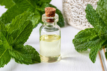 A bottle of essential oil with fresh peppermint leaves