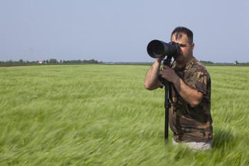 a photographer in a grain field with a telephoto lens