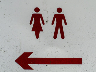 Male and female signs and directional arrow, color red, white surface.