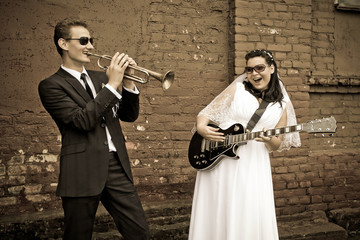 The groom plays the saxophone and the bride on the electric guitar on the wedding day